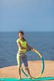 Woman rotates hula hoop on summer beach Stock Photo