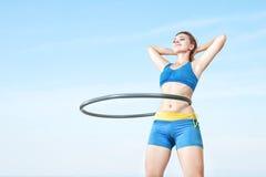 Woman rotates hula hoop Stock Image
