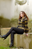 Woman on rough background. Sitting young fashion woman on rough dirty old background Stock Photo