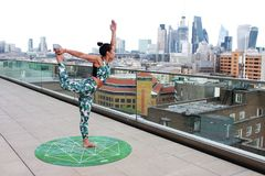 Woman on Round Green Yoga Mat Position in Right Leg High and Left Hand Upright Posiiton royalty free stock photos