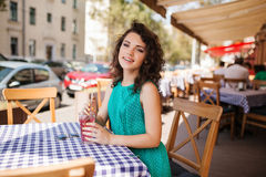 Woman in round sunglasses with cocktail at cafe terrace having fun. Young beautiful woman in round sunglasses with curly hair with cocktail at the terrace of stock photos