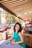Woman in round sunglasses with cocktail at cafe terrace having fun. Young beautiful woman in round sunglasses with curly hair with cocktail at the terrace of stock photography