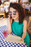 Woman in round sunglasses with cocktail making order at cafe stock images