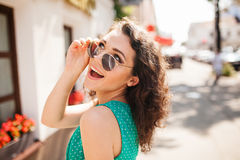 Woman in round sunglasses smiling over shoulder in city street stock image