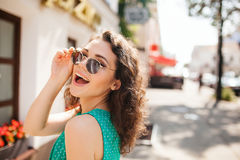 Woman in round sunglasses smiling over shoulder in city street royalty free stock photos