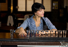 Woman with a row of vodka shot glasses. Lined up in front of her sitting at a bar counter smiling and looking away to the side stock image