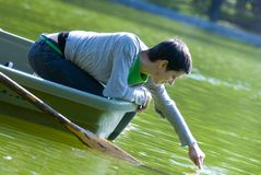 Woman in rowboat touching water  Royalty Free Stock Image