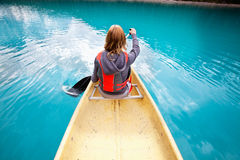 Woman rowing boat. Rear view of woman rowing boat on calm water royalty free stock photography