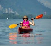 Woman rowing in kayak. Young woman paddling kayak on Lake Brienz, Interlaken, Switzerland Stock Photos