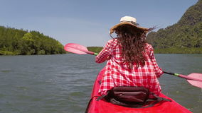 Woman rowing kayaking in lagoon action camera pov back rear view of girl paddling on kayak boat. In sea stock video footage