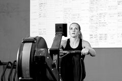 Woman on rowing machine - crossfit workout Royalty Free Stock Photos