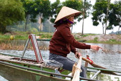 Woman rowing a touristic boat on Ngo Dong river. Tam Coc. Ninh Binh. Vietnam Royalty Free Stock Images
