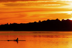 Woman rowing and training at sunset. Woman rowing and training at orange sunset Royalty Free Stock Photography
