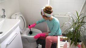 Woman with a rubber glove cleans a toilet bowl. Using means for cleaning stock footage