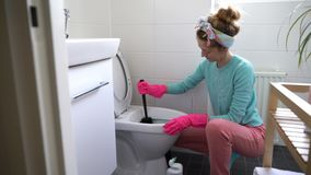 Woman with a rubber glove cleans a toilet bowl. Using means for cleaning stock video footage