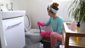 Woman with a rubber glove cleans a toilet bowl. Using means for cleaning stock video
