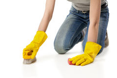 Woman in rubber glover with brush cleaning floor Royalty Free Stock Image