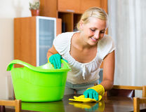 Woman in rubber gloves cleaning indoors. Cheerful blonde girl in rubber gloves cleaning indoors stock photography