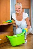 Woman in rubber gloves cleaning indoors. Cheerful smiling blonde woman in rubber gloves cleaning at home stock image