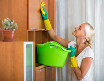 Woman in rubber gloves cleaning indoors. Cheerful young blonde woman in rubber gloves cleaning at home royalty free stock photos