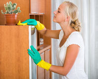 Woman in rubber gloves cleaning indoors. Ordinary young woman in rubber gloves dusting furniture at home stock image