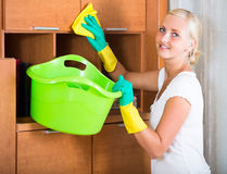 Woman in rubber gloves cleaning indoors. Smiling blonde girl in rubber gloves dusting furniture indoors stock photo