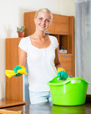 Woman in rubber gloves cleaning indoors. Smiling blonde girl in rubber gloves dusting furniture at home royalty free stock photo