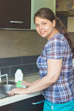 Woman in rubber gloves washing kitchenware Royalty Free Stock Photos