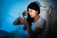 Woman rubbing eyes with using smartphone. Woman rubbing her eyes feel painful with using smartphone sitting on bed sleeping at night. Mobile addict concept royalty free stock photos