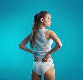 Woman rubbing her back. Lumbago. Back pain. Young attractive female holding her sore loin over blue background Stock Image
