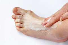 A woman rubbing her foot with a pain ointment Royalty Free Stock Photography