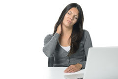 Woman rubbing her neck to relieve stiffness. Attractive young businesswoman sitting at her laptop rubbing her neck with a grimace to relieve stiffness after Stock Image