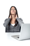 Woman rubbing her neck to relieve stiffness. Attractive young businesswoman sitting at her laptop rubbing her neck with a grimace to relieve stiffness after Royalty Free Stock Images