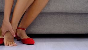 Woman rubbing tired swollen feet, varicose veins. Female taking red shoes.
