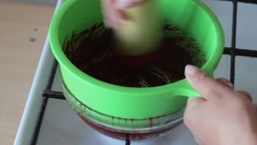 A woman rubs boiled sugar-cooked cranberries in a colander. Prepares mashed potatoes for marshmallow. A woman rubs boiled sugar-cooked cranberries in a colander stock video