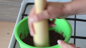 A woman rubs boiled sugar-cooked cranberries in a colander. Prepares mashed potatoes for marshmallow. A woman rubs boiled sugar-cooked cranberries in a colander stock video footage