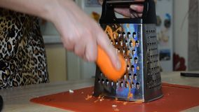Woman rubs carrots on a grater in slow motion.