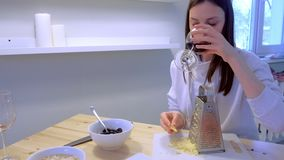 Woman rubs cheese on grater at home and drinks red wine in the kitchen. Couple cooks dinner. Woman rubs cheese on grater at home and drinks red wine in the stock footage