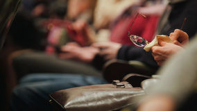 Woman rubs glasses i n concert hall Royalty Free Stock Images