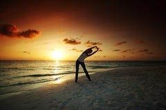 Woman run. Along the sea coast of sunrise behind Stock Photo