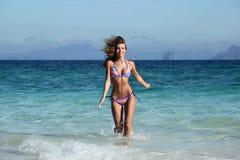 Woman run on beach. Beautiful fit woman in bikni run on tropical beach Royalty Free Stock Image