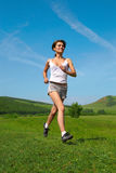 Woman run on green grass Stock Photography