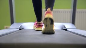 Woman run on a treadmill. Close-up legs shot. Running on a walking machine. Healthy lifestyle concept stock footage