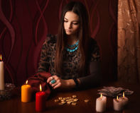 Woman with runes and divination cards in room. Young woman with runes and divination cards in room Royalty Free Stock Photo