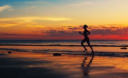 Woman runing  along the sea coast Royalty Free Stock Photography