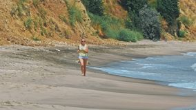 Woman runing on the beach stock video
