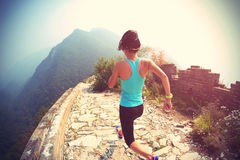 Woman runner athlete running on trail at chinese great wall stock photography