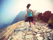 Woman runner athlete running on trail at chinese great wall stock image