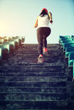 Woman runner athlete running up on stairs. Stock Photo