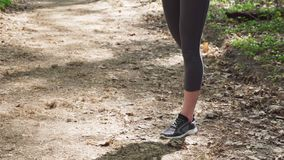 Woman runner doing warm-up exercise before jogging. In forest stock video